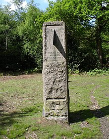 "A standing stone in a grassy field surrounded by trees. The stone contains a vertical sundial centered on 1 o'clock, and is inscribed ""HORAS NON NUMERO NISI ÆSTIVAS"" and ""SUMMER TIME ACT 1925""."