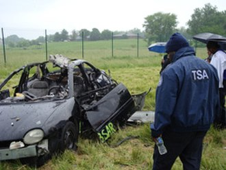 Car bomb - TSA officers view the post-blast remains of a Chrysler Neon after an explosive was detonated inside it during training.