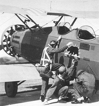 California Air National Guard - Preparing for a target towing mission at Camp Merriam, now Camp San Luis Obispo, in 1933. Captain Miller of the 115th Observation Squadron boards an O-38 as mechanics adjust the towing mechanism.