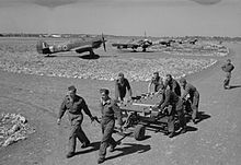a black and white photograph of men pulling a trolley, with aircraft dispersed in the near background