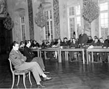 An American soldier interprets for a witness, a German, to the character of one of the defendants of the Borkum Island massacre. The witness is being addressed by a lawyer (standing, center right) of the defense counsel.
