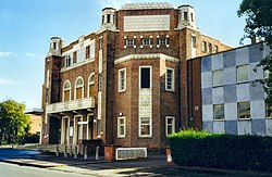 A large brick building. A more modern extension goes off to the right. The building sits on the corner of a street, and is seen in bright, sunny weather.