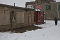 An Afghan boy, left, takes cover from the falling snow as U.S. Soldiers, stationed on Combat Outpost (COP) Zormat, patrol his village in Paktya province, Afghanistan, Feb. 3, 2012 120203-A-LP603-073.jpg