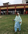 An aged woman coming out of the polling booth after casting her vote while a large crowd waiting to cast their vote for the first phase of General Election 2009 at a booth in R S Pura, Jammu on April 16, 2009.jpg