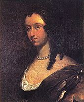 Dark portrait of woman with should length curly black hair and pearl necklace