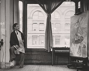"Yasuo Kuniyoshi - Kuniyoshi working on his painting ""Upside Down Table and Mask"" in his studio near Union Square at 30 East Fourteenth Street in New York, New York"