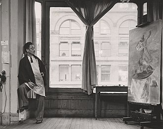 "Yasuo Kuniyoshi - Kuniyoshi working on his painting ""Upside Down Table and Mask"" in his studio near Union Square at 30 East Fourteenth Street in New York City"
