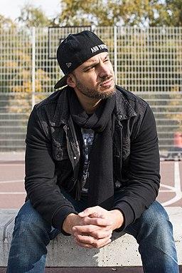 Ein junger Mann (Ben Salomo) sitzt vor einem Außenbaskettballplatz auf einer Betonbank