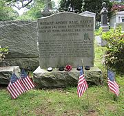 Large gravestone. On the mantle of the grave is four hockey pucks and a rose between them. Four small American flags are in the ground in front of the grave as well