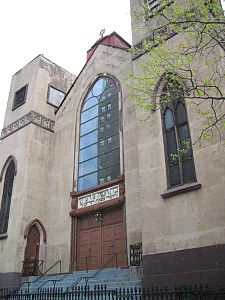 Most of the front of a three-story building is visible. It shows two rectangular towers, one on each side of a recessed bay, all clad in tan stucco. The towers have pointed arched windows on the bottom and square ones on top. The bay has four wooden doors at the bottom and a sign with Hebrew writing on top of them, surmounted by large arched multi-paned window. Atop the roof of the bay is a small metal Star of David.