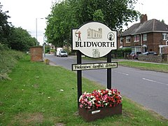 Sign saying Blidworth welcomes careful drivers, with images of Robin Hood, the church and a coal mine
