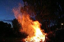 Un falò in una zona rurale dell'Australia, con molte braci che sfrigolano al vento.