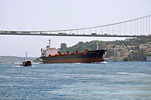 A large ship passes underneath a suspension bridge; hilly terrain and historic walls can be seen in the background.