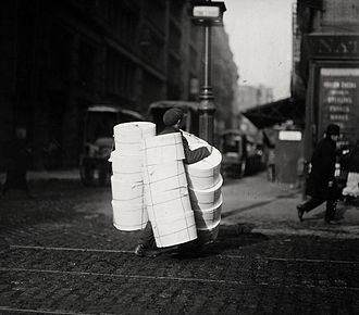 Hat box - A boy carrying an assortment of hat boxes in New York City c. 1912