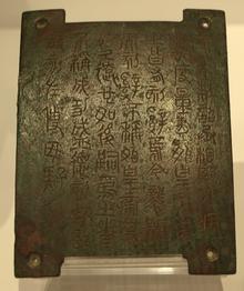 Photographie d'une petite plaque de bronze gravée de sinogrammes anciens.