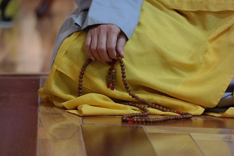 Buddhist mala beads in nun's hand