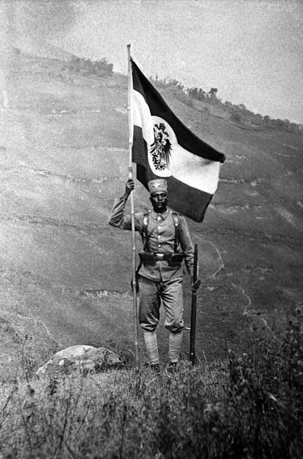 An East African Askari soldier holding Germany's colonial flag Bundesarchiv Bild 105-DOA6369, Deutsch-Ostafrika, Askari.jpg