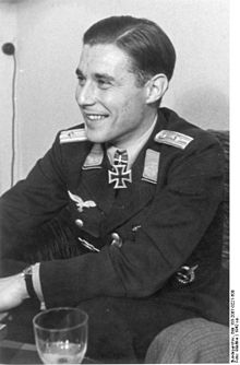 Prince Zur Lippe-Weißenfeld is casually sitting and smiling. The Knight's Cross of the Iron Cross, German Cross in Gold and Pilots Badge can be seen on his uniform.
