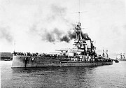 A large warship steams at low speed; gray smoke drifts from the smoke stack