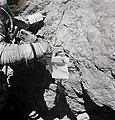 Charles M. Duke Jr. examines closely the surface of a large boulder.jpg