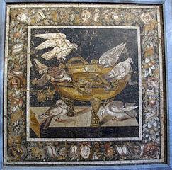 Doves drinking at a golden basin