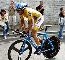Een man met gele Kleding en Een blauwe helm, Rijden op Een fiets.  Op de Achtergrond sommige toeschouwers.