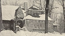 Sepia image of a small snow-covered stone cottage surrounded by tall trees