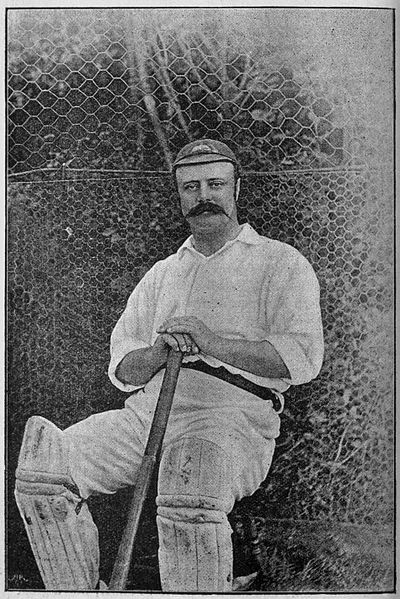 Man with moustache seated on chair holding cricket bat.