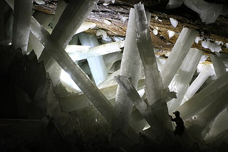 Gypsum crystals of the Naica cave. Note person for scale. Author: Alexander Van Driessche