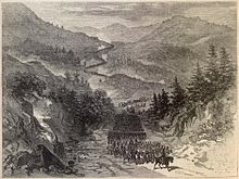 A lithograph in black and white of a road winding through a mountainous region.  An army of thousands is marching along the road, led by a military officer on a horse.