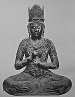 Front view of a statue depicted wearing a crown and showing the Vajra Mudrā, enclosing the index finger of the left hand with the fist of the right hand.