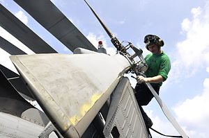 Defense.gov News Photo 110809-N-ZZ999-018 - U.S. Navy Petty Officer 2nd Class Branden Rucker performs maintenance to control corrosion on the tail rotor of an SH-60F Seahawk helicopter.jpg