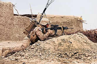 M27 Infantry Automatic Rifle - A U.S. Marine armed with an M27 fitted with a Harris bipod and a 3.5x Squad Day Optic covers his team in Afghanistan in March 2012.