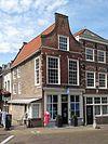 foto van Hoekpand Oudekerkstraat met tot tuitgevel gewijzigde topgevel en boven de verdiepingsvensters geblokte ontlastingsbogen. Tegen de gepleisterde zijgevel een pothuis