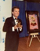 A smiling, formally clad man holding a Grammy Award.