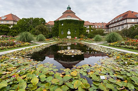 Pond of the Schmuckhof (Jewel Courtyard) with the main building in the background, Botanical Garden, Munich, Germany. Although the Botanical Garden in Munich as institution exists since 1809 it moved to the current location exactly 100 years ago.