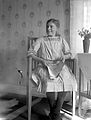 En flicka sitter i en stol vid ett bord. I knät har hon en tidning - Nordiska Museet - NMA.0057507.jpg