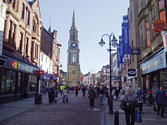 Falkirk High Street with the Falkirk Steeple dominating the centre of the picture. Shops to the left and right are visible with many shoppers on the pedestrianised street.