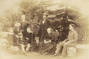 A group of figures surrounds the seated Emperor and Empress in this outdoor photograph.