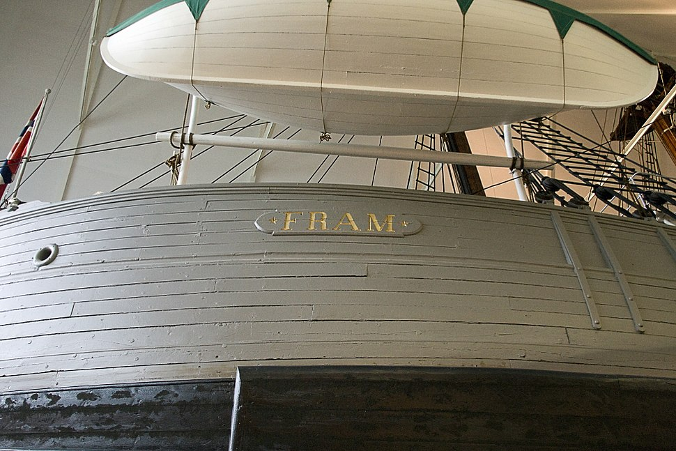 Photograph showing part of a ship's curved hull, bearing the name FRAM. A small lifeboat has been slung above the ship's rail.