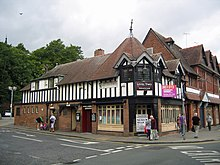 A two-storey building seen from the corner; the lower storey is brick and the upper storeys timber-framed.  The left side extends further than the right and contains the public conveniences, with two doorways on the ground floor and a long dormer above.  On the corner is a doorway with windows on each side; above are three windows extending round the corner, each with a gable.  Behind these is a tiled spire.