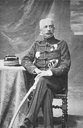 A portrait of General Lyautey in military uniform, seated at a small table