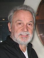 Headshot of a bearded man wearing an unbuttoned black collared shirt over a white T-shirt.