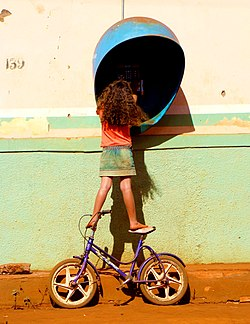 Girl on bike at payphone.jpg