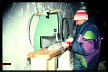 Scientist standing at a bench, sawing an ice core