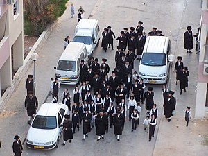 A group of people clad mostly in black, some partially in white, walking along a street between several white vehicles, seen from above and in front