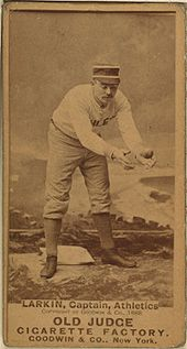 A baseball player is standing, focusing his attention on catching a baseball.