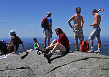 Six people on a rocky surface. Three are sitting and three are standing. One is wearing a backpack. At the right are two shirtless men with a backpack in between them on the rock.