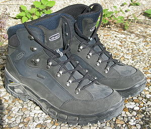 Two dark gray ankle-covering boots covered in suede and cloth with laces going through hooks rather than eyelets, on a pebbly surface