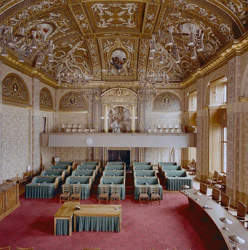 interieur overzicht vergaderzaal vanaf tribune met gerestaureerde plafondschilderingen